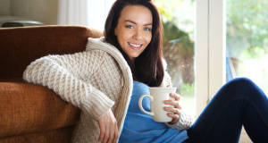 Attractive young lady relaxing at home with cup of coffee